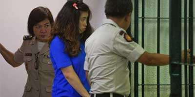 Noppawan Tangudomsuk is detained by criminal court officers at the criminal court in Bangkok | Photo: Reuters