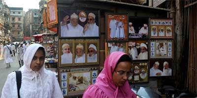 Women from the Bohra community walking past a shop selling pictures of their religious leaders, outside a mosque in Mumbai. | AFP Photo